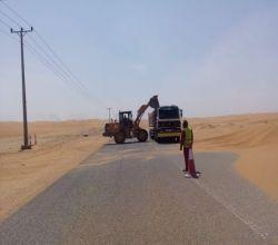 بالصور : الشركة المسؤولة عن صيانة الطريق تزيل رمال عرق مريصيص